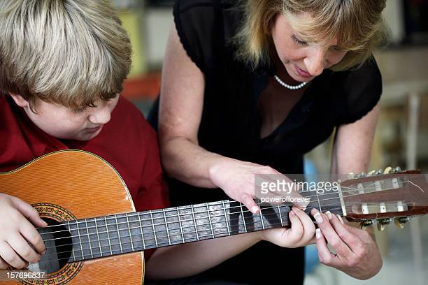 Boy Learning to Play Guitar in Music Class