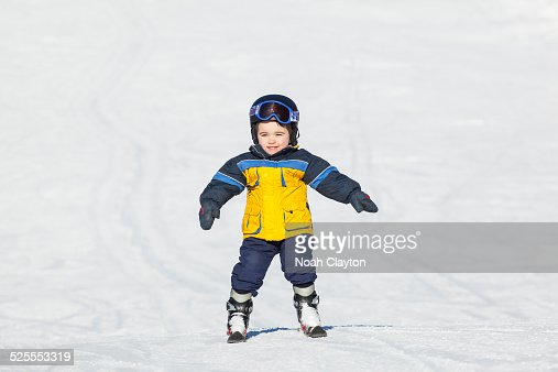 Boy learning to ski and smiling