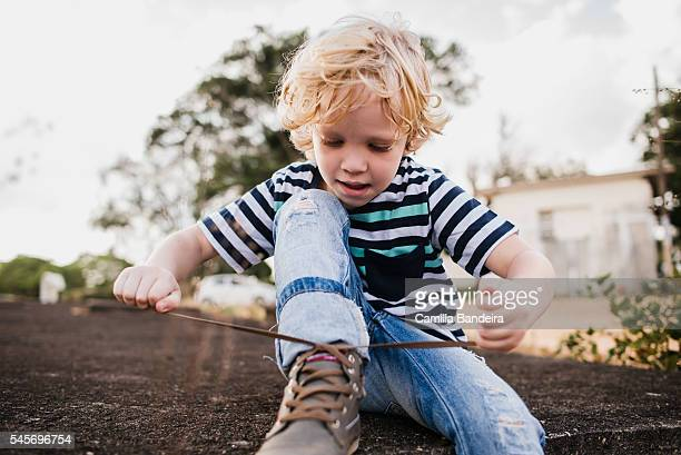 Boy learning to tie his shoelaces