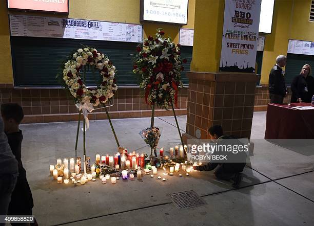 A boy leaves a candle at a memorial at a candlelight vigil at the San Manuel Stadium in San Bernardino California December 3 2015 for victims of the...