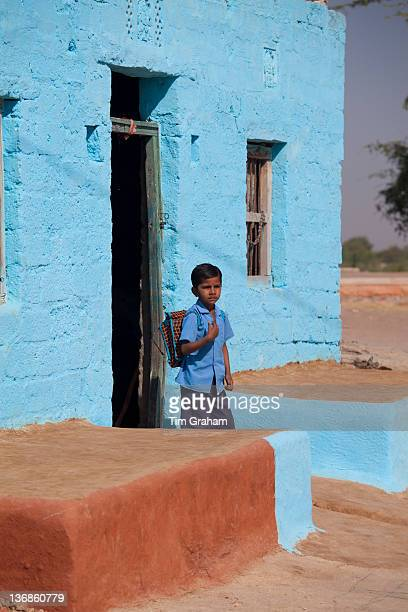 Boy leaves home in Hindu Brahman high caste village of Dhudaly heading for school in Rajasthan Northern India