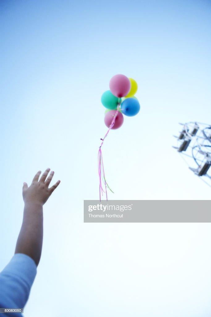 boy letting go of balloons  : Stock Photo