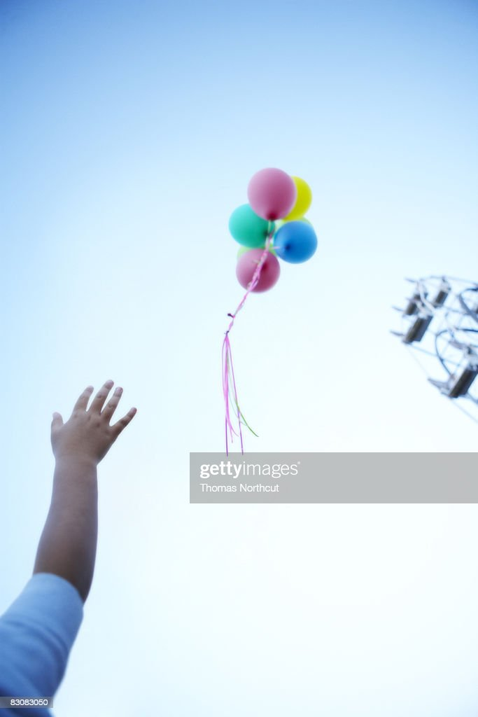 boy letting go of balloons