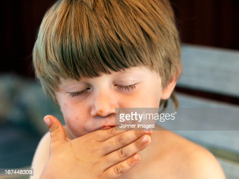 Boy licking his fingers : Stock Photo