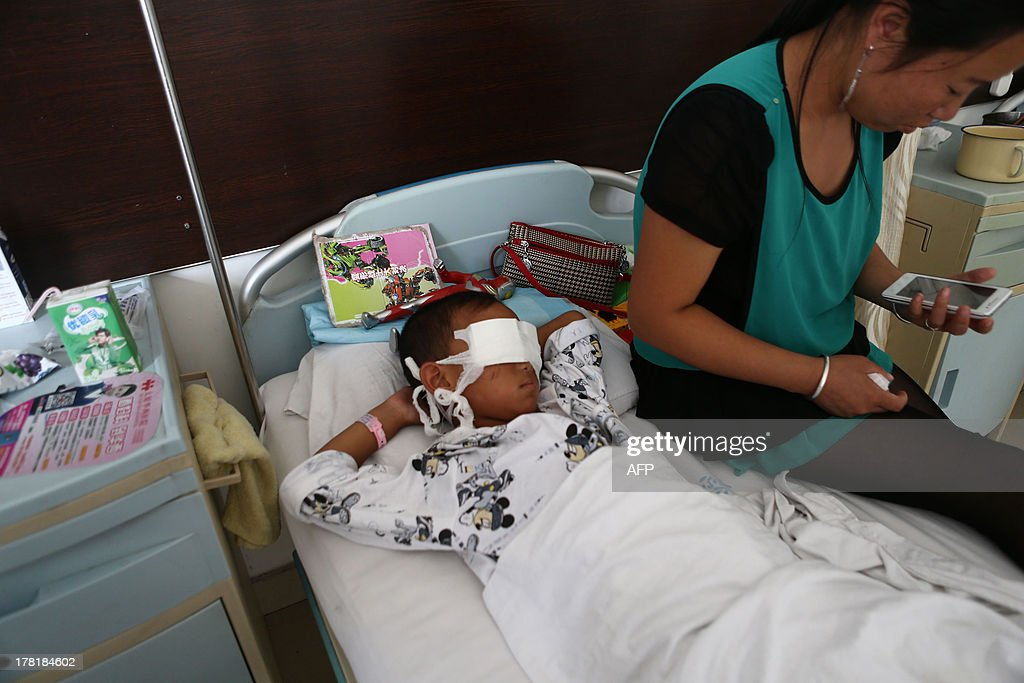 A boy (L) lies on his hospital bed with his eyes covered with bandages as his mother sits next to him at a hospital in Taiyuan, north China's Shanxi province on August 27. The six-year-old boy from northern China was drugged and had his eyes gauged out, reports said, in a gruesome attack that may have been carried out by a ruthless female organ trafficker. CHINA