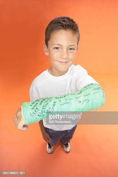 Boy (7-9) lifting arm to show cast, elevated view