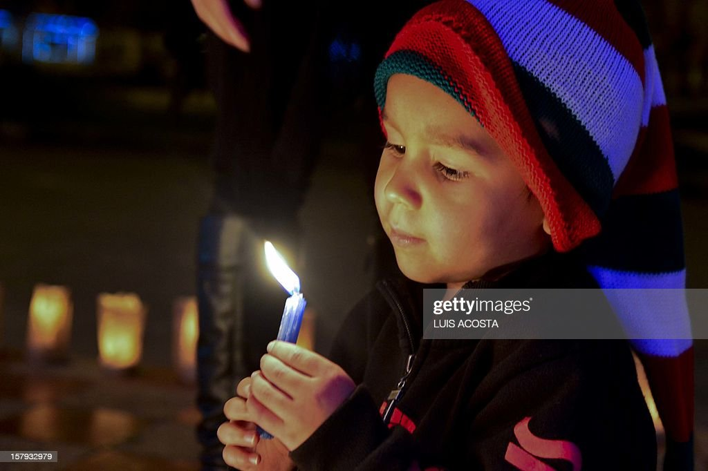 A boy light candles during the Day of the Little Candles in Bogota on December 7, 2012 as Colombia starts the Christmas season. AFP PHOTO/Luis Acosta