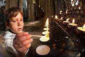 Boy lighting candles in cathedral