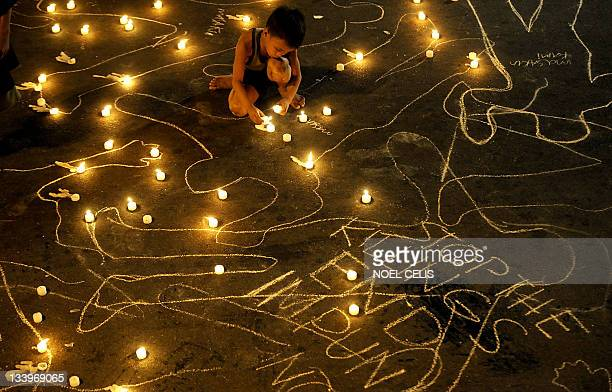 A boy lights a candle during a vigil to commemorate the second anniversary of the Maguindanao massacre near the Malacanang palace in Manila on...