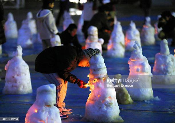 A boy lights a candle placed in a snow statue of Ksitigarbha to mark the 20th anniversary at Yasui Elementary School on January 17 2015 in...