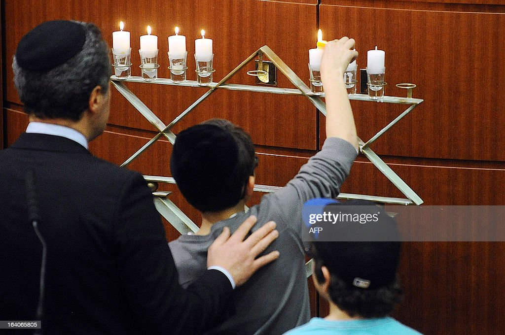 A boy lights candles during an homage, on March 19, 2013, in the 'Espace du judaisme' in Toulouse, southwestern France, to those slain by Al-Qaeda-inspired gunman Mohamed Merah whose shooting spree in and around Toulouse left seven people dead in March 2012. GABALDA
