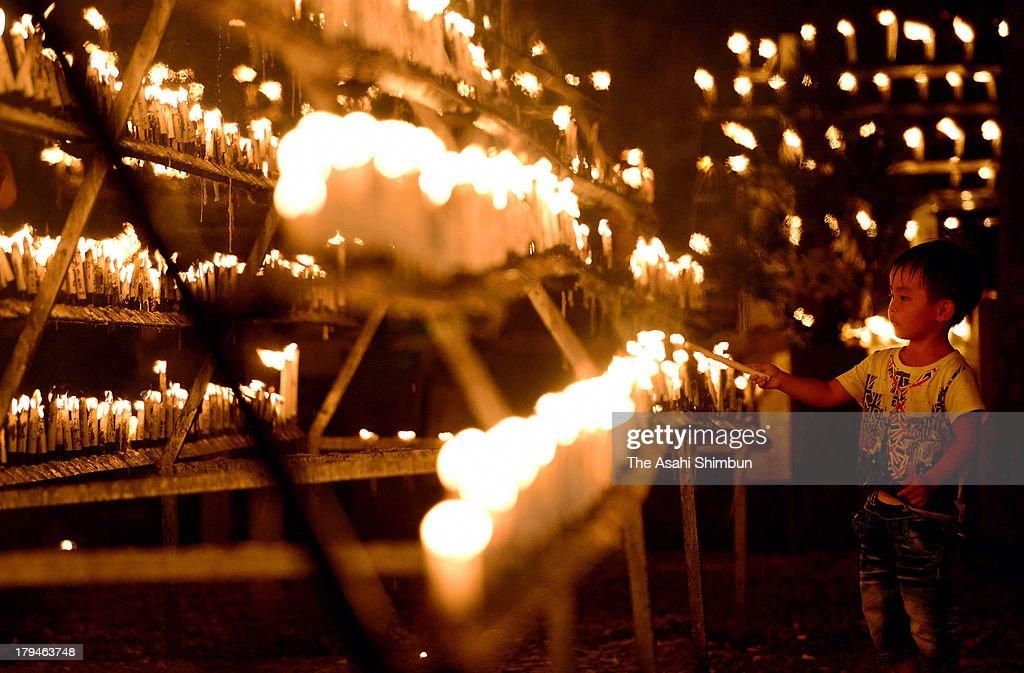 A boy lights candles during the Kento 'Dedication of Light' Festival at Hikarisanboko Shrine on September 3, 2013 in Hashimoto, Wakayama, Japan.