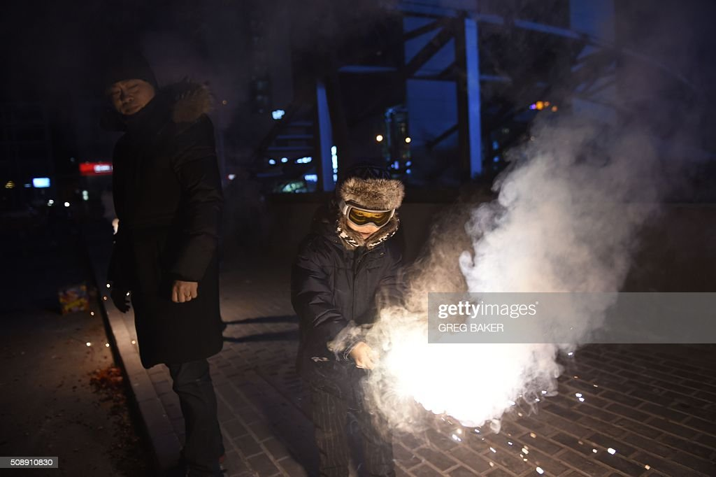 A boy lights fireworks as his father looks on in Beijing on February 7, 2016, the eve of the Lunar New Year. China marks the beginning of the Lunar New Year, the Year of the Monkey, on February 8. AFP PHOTO / GREG BAKER / AFP / GREG BAKER