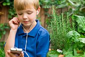 Boy listening to music player in the garden