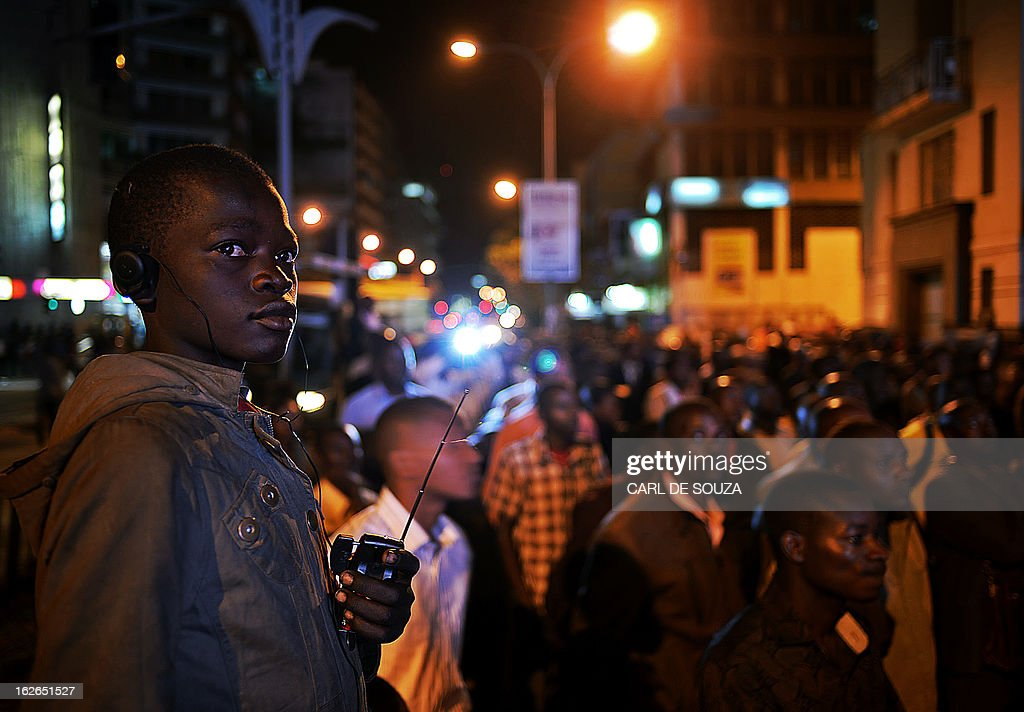 A boy listens to a radio as he stands with a large crowd which gathered to watch the second and last televised debate for the 2013 Kenya elections on a large screen in Central Nairobi on February 25, 2013. Kenyans will vote for a new leader on March 4, 2013. AFP PHOTO/Carl de Souza
