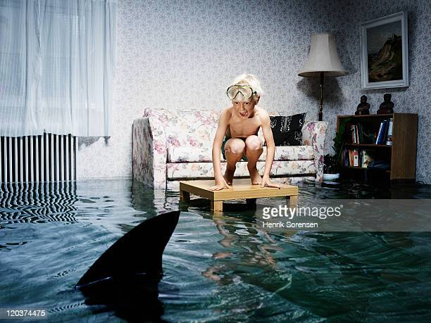boy lookin at shark fin in flooded room