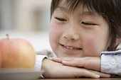 Boy looking at an apple
