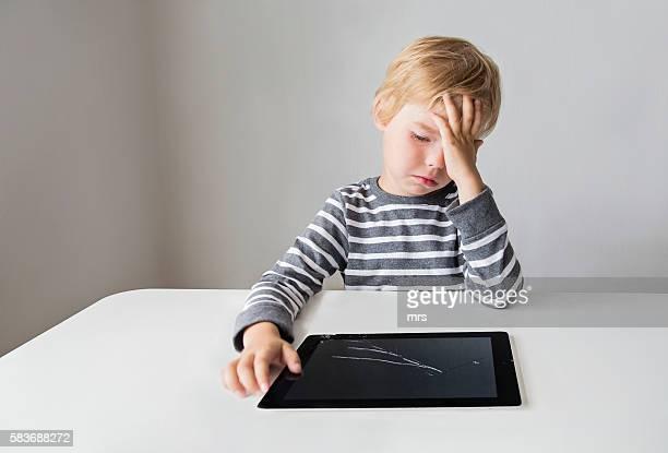 Boy looking at broken digital tablet