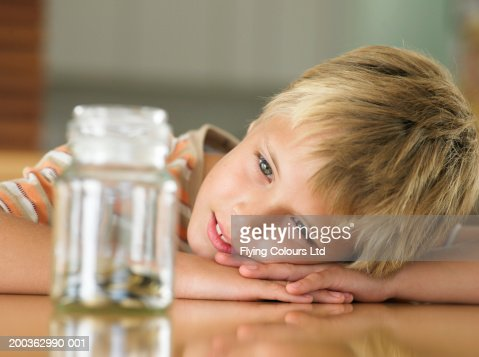 Boy (7-9) looking at coins in jar, close-up : Stock Photo