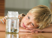 Boy (7-9) looking at coins in jar, close-up