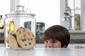 Boy (3-5) looking at cookie jar on kitchen counter