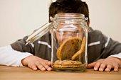 Boy looking at cookies in jar