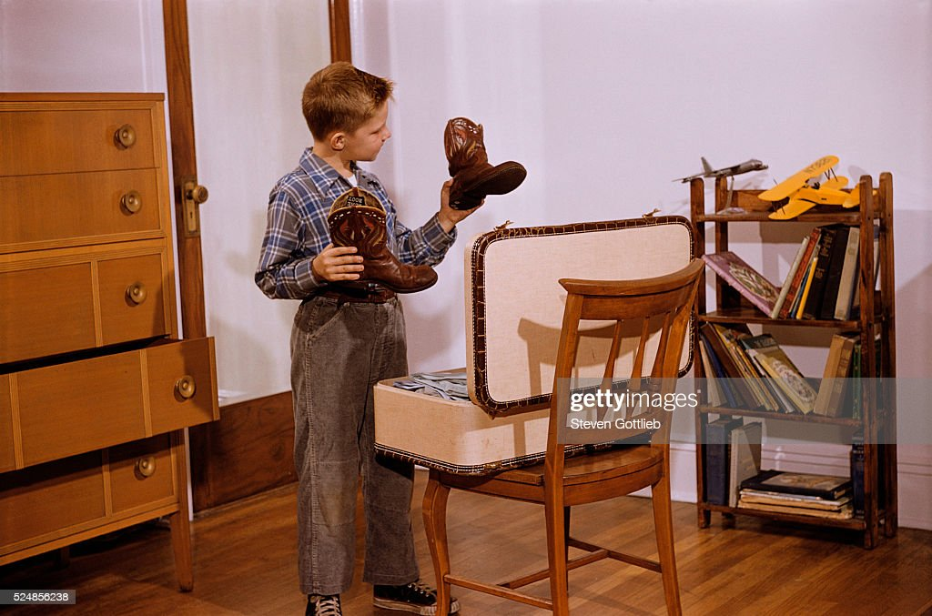 Boy Looking at Cowboy Boots Pictures | Getty Images