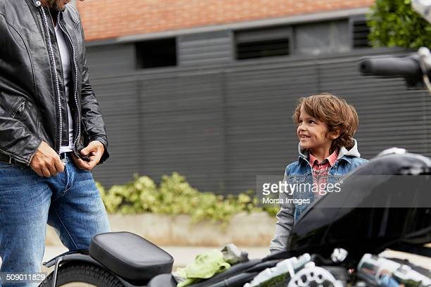 Boy looking at father wearing jacket by motorbike