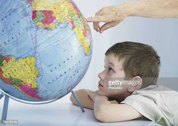 Boy looking at globe, elderly person's hand pointing to spot on globe