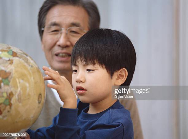 Boy (5-7) looking at globe with grandfather