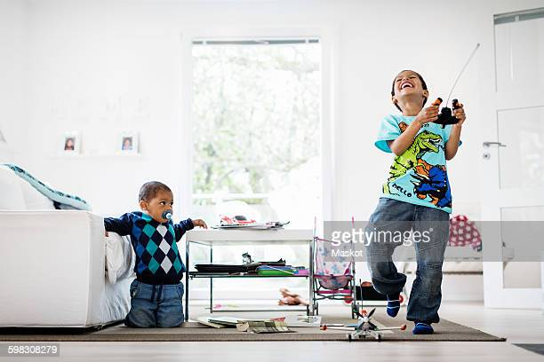 Boy looking at happy brother holding remote of model airplane at home