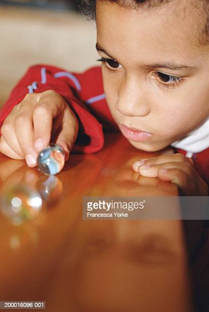 Boy (7-9) looking at marble on table, close-up