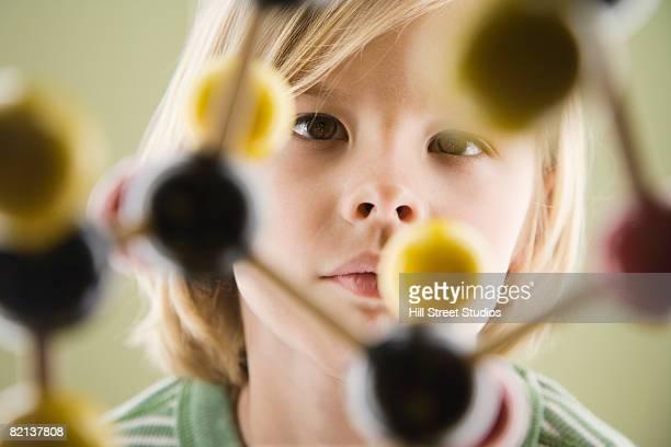 Boy looking at molecular model