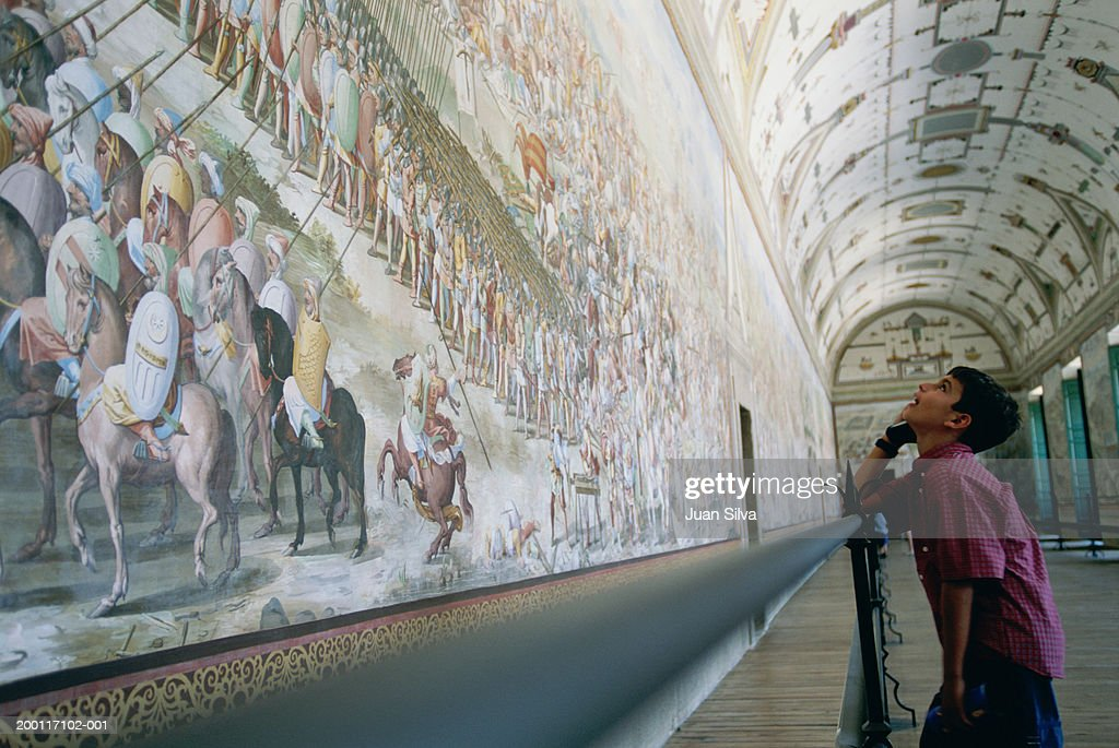 Boy (10-12) looking at mural in Escorial Palace : Stock Photo