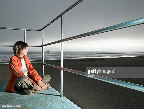 Boy (12-14) looking at ocean from lifeguard railing, dusk