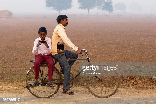 Boy looking at smartphone on back of bicycle