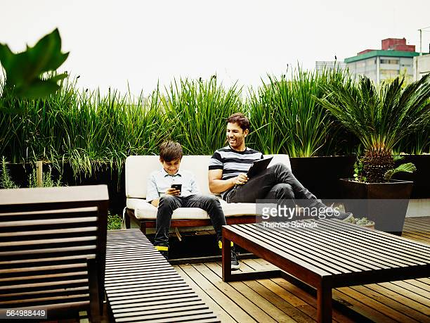 Boy looking at smartphone sitting with father