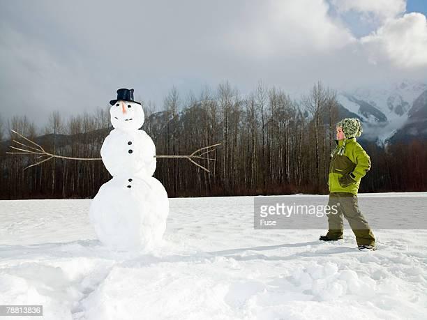 Boy Looking at Snowman