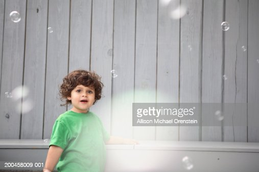 Boy (2-4) looking at soap bubbles : Stock Photo