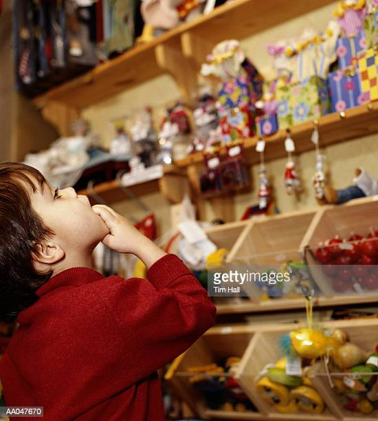 Boy (3-5) looking at toys in shop, side view