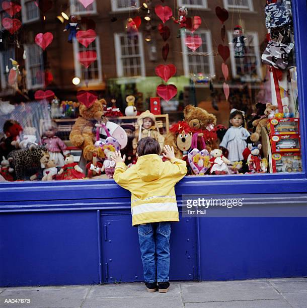 Boy (3-5) looking at toys in toy shop window, rear view