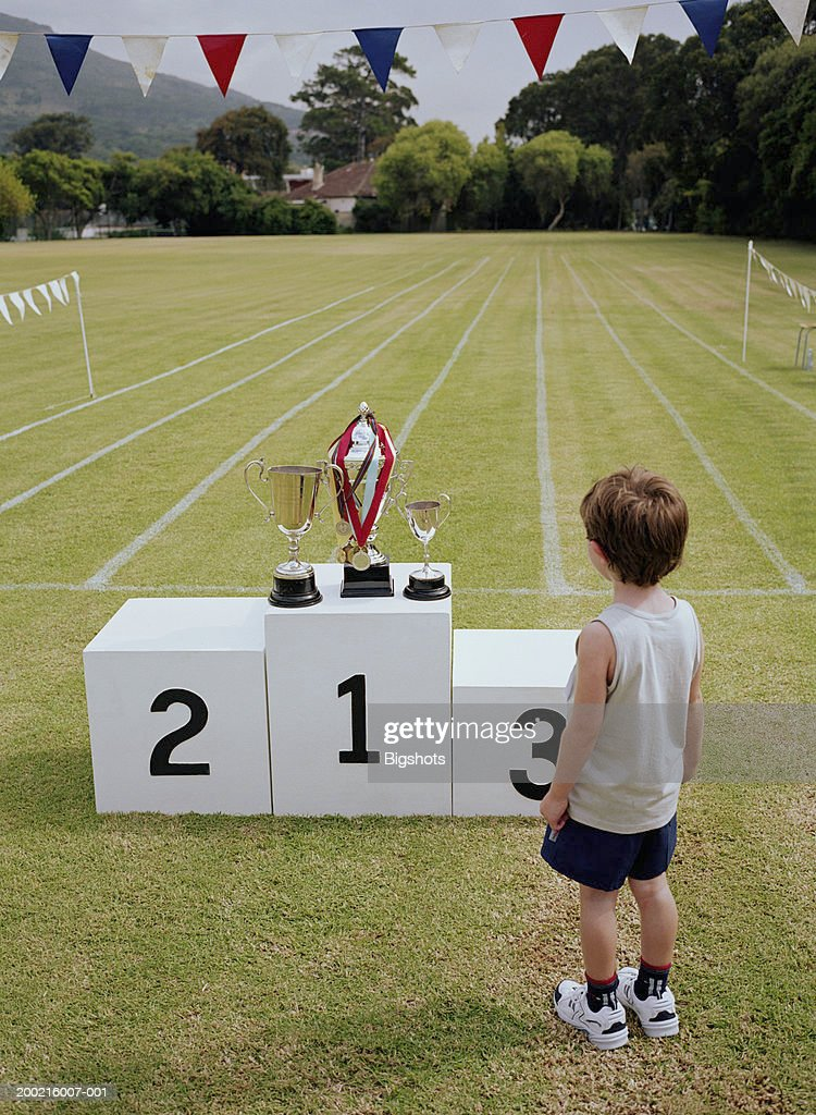 Boy (3-5) looking at trophies on winners podium in sports field