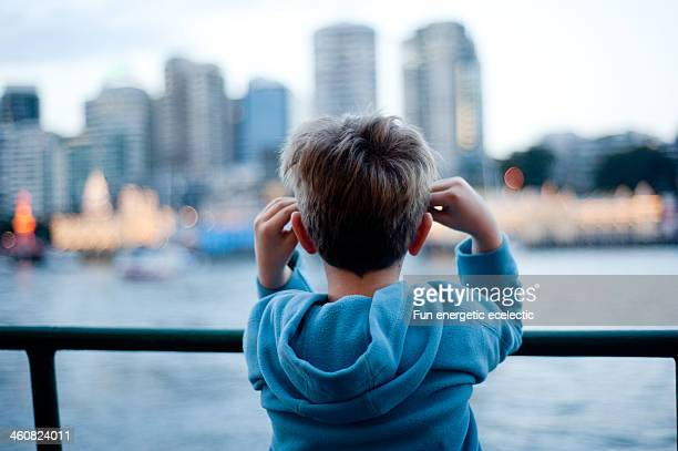 Boy looking at view over water of a city