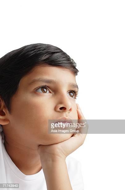 Boy looking away, hand on chin