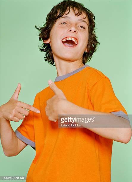 Boy (10-12) looking away, smiling