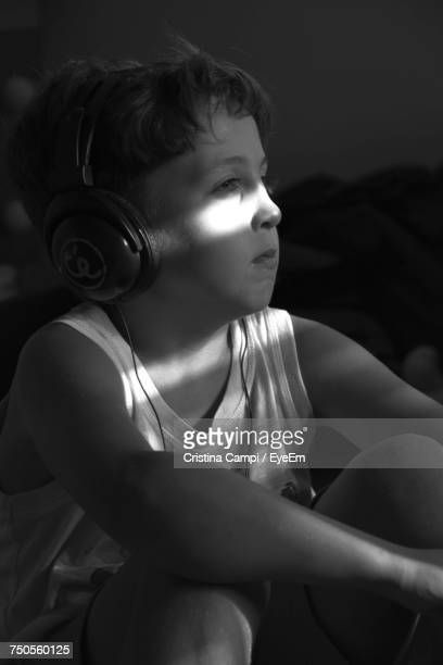 Boy Looking Away While Listening Music Through Headphones At Home