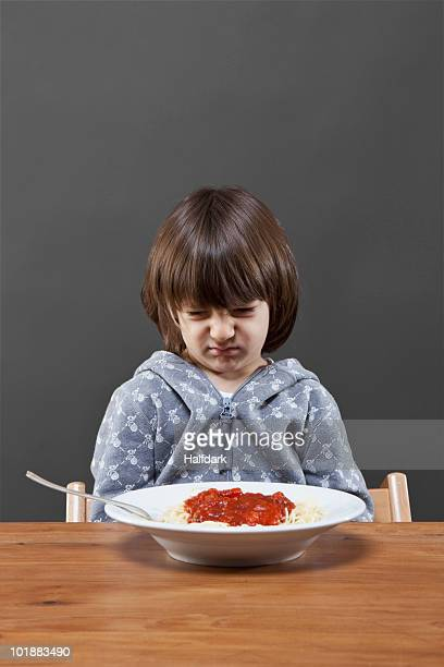 A boy looking down at a bowl of spaghetti in disgust, studio shot