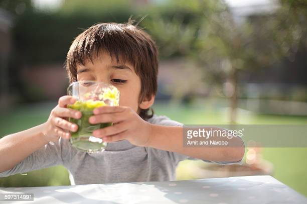 Boy looking down drinking green smoothie