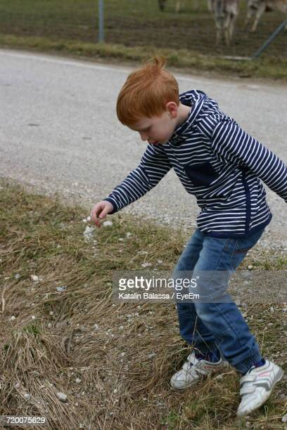 Boy Looking Down While Playing On Grassy Field By Road