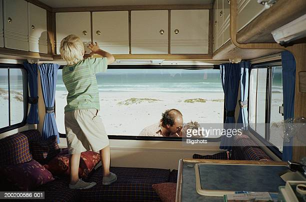 Boy (6-8) looking in cupboard of campervan, couple outside kissing